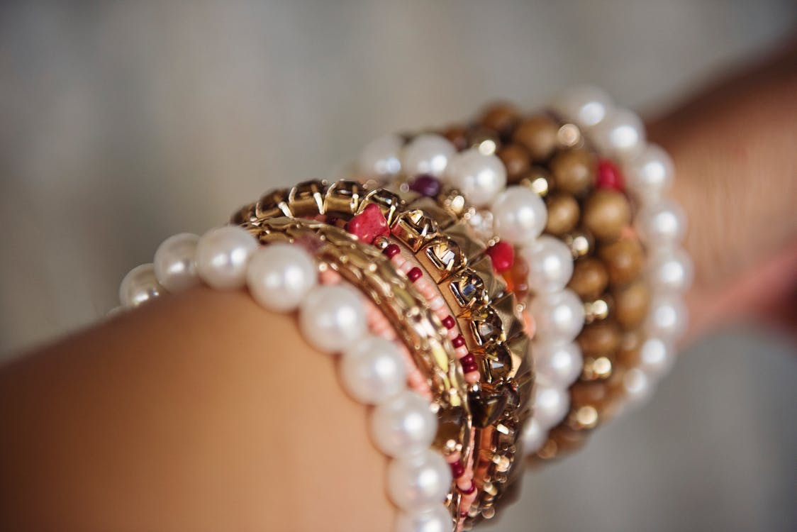 image of gold and pearl bracelets on ladies arm